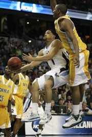 Villanova's Scottie Reynolds, center, flies by the Siena defense for a layup. Reynolds led the Wildcats with 25 points in their 84-72 second-round victory Sunday in Tampa, Fla.