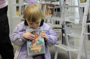 "Brylie Prawl, 2, inspects the DVD ""Tarzan"" at the Lawrence Public Library, 707 Vt. Renting books, movies and music from the local library is free."