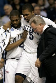 Villanova's Casiem Drummond (5) gets help from teammate Shane Clark (22) and trainer Jeff Pierce. Drummond, Villanova's tallest player at 6-foot-10, broke his ankle against Siena and will not play Friday against Kansas.