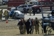 Emergency crews carry an injured passenger to be air lifted to KU Medical Center late Friday morning. An accident involving a 2002 Nissan and a pickup truck at the intersection of Kansas Highway 32 and the entrance to northbound K-7.