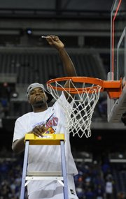 KU forward Darnell Jackson hoists a piece of net after KU advanced to the Final Four on Sunday.
