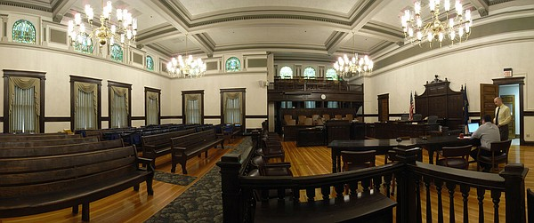 Douglas County clerk Jamie Shew, seated at far right, and Keith Clark, deputy clerk, standing, work inside the historic courtroom in the Douglas County Courthouse, 1100 Mass. The courtroom maintains the grandeur of its period but is no longer used for regular trials. This stitched panorama photograph is taken from the public entrance doors to the courtroom chambers on the north wall.