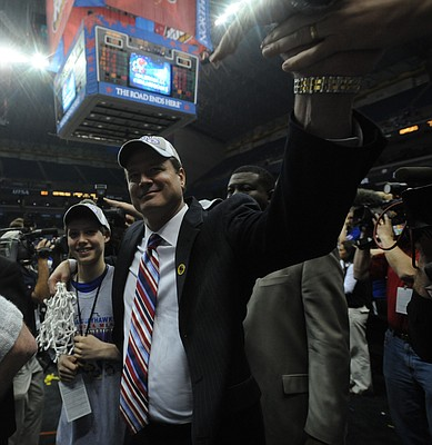 Kansas head coach Bill Self slaps hands with fans as he makes his way from the court with his arm around his son Tyler Self following the Jayhawks National Championship win over Memphis Monday, April 7, 2008 at the Alamodome in San Antonio.