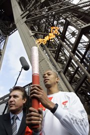 Stephane Diagana, the 400-meter world champion in 1997, carries the Olympic torch at the beginning of its relay from the first floor of the Eiffel Tower on Monday in Paris. About 3,000 French police - on motorcycles, in jogging gear and on skates - were mobilized to protect the Olympic torch relay as it departed from the Eiffel Tower.