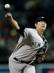 New York starter Chien-Ming Wang delivers against Boston during the first inning. Wang pitched a complete game and gave up only two hits in the Yankees' 4-1 victory over the Red Sox on Friday in Boston.