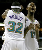 New Orleans' Hilton Armstrong (12) celebrates with Julian Wright as the Hornets pulled away from the Clippers, 114-92. With the victory, the Hornets clinched the Southwest Division title Tuesday night in New Orleans.