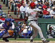 Los Angeles' Gary Matthews Jr. launches a three-run double. The Angels defeated the Rangers, 7-4, on Tuesday in Arlington, Texas.