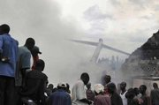 Rescue workers and onlookers gather at the site of a plane crash in Goma, Congo. A passenger plane carrying 85 people crashed into a crowded neighborhood in the eastern Congo town on Tuesday. Most if not all of the passengers aboard the plane survived but several people on the ground were killed.