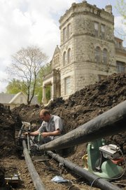 Jeron Fuller, of Evans Energy Development in Paola, connects pipes Thursday to a geothermal system that will use the heating and cooling power of the Earth to reduce utility expenses at the Castle Tea Room, 1307 Mass.