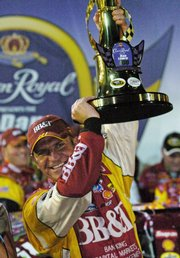 Clint Bowyer holds the winners trophy in Victory Lane. Bowyer won the NASCAR Crown Royal 400 Sprint Cup on Saturday at the Richmond International Raceway in Richmond, Va.