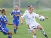 Lawrence High sophomore Olivia Dykes looks to push the ball up field against Olathe South during the first half, Monday, May 5, 2008 at YSI.