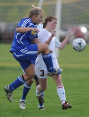 Lawrence High junior Becky Davis collides with Olathe South junior Kaylee Sextro during the first half, Monday, May 5, 2008 at YSI.