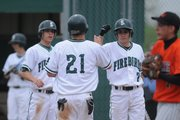 Free State's Alex Hardman, right, knocks fists with teammate E.J. Swanson after Swanson scored. Hardman followed up with a two-run home run.