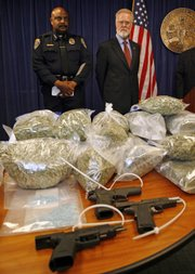 San Diego State University president Stephen Weber, right, and SDSU chief of police John Browning, left, stand over a guns and drugs seized during the arrest of 96 people on drug charges Tuesday in San Diego. Seventy-five SDSU students and 21 nonstudents were arrested after an undercover investigation of the college drug ring.