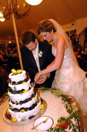 "J.P. and Corey Marchetti cut her lemon-flavored wedding cake at their wedding reception catered by the contestants of Bravo&squot;s ""Top Chef,"" a cooking reality show. The bride is a Lawrence native who was married in Chicago."