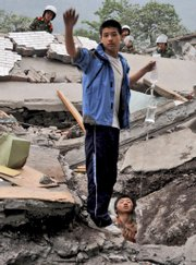 A student helps his schoolmate stranded in the ruins of a high school in Beichuan county, in southwest China's Sichuan Province. The death toll from a powerful earthquake climbed today to at least 10,000 as rescue efforts entered a second day.