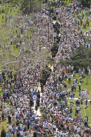 Members of Kansas University's Class of 2008 are greeted by friends, family and well-wishers Sunday as they walk down Campanile hill into Memorial Stadium.