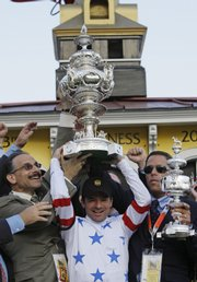 Jockey Kent Desormeaux holds the trophy with Richard Schiavo, left, and Michael Iavarone of IEAH Stable following Big Brown's victory in the Preakness Stakes.