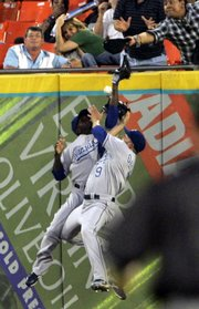 Kansas City right fielder David DeJesus (9) and center fielder Joey Gathright collide as they attempt to catch a hit by Florida's Mike Jacobs. Jacobs collected a triple on the play, and the Marlins defeated the Royals, 7-3, on Saturday night in Miami.