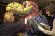 "From Left, Susie Lawler, Pat Woelk and Kris Wyman, put finishing touches on their Jayhawk, ""Chip of the Old Hawk."""