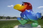 "The ""Peace, Love and Daisy Hill forever"" Jayhawk by Susan Younger and Valerie Spicher has been repaired, repainted and is back to strutting its feathers in front of the Douglas County Bank at 31st and Iowa. The Jayhawk, which was placed at its new spot Tuesday, had suffered significant vandalism when perched at Sixth Street and Folks Road, and its paint had faded significantly. The new paint is auto paint."