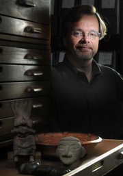"John Hoopes, Kansas University associate professor of anthropology, is pictured Thursday with real pre-Colombian artifacts from Mexico and Central America in Spooner Hall. Hoopes believes that the crystal skulls, popularized by the latest ""Indiana Jones"" movie, were probably crafted in Europe in the late 1800s."