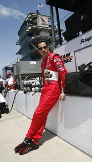 IRL driver Helio Castroneves watches practice from the pits in this file photo from May 17. The Brazilian hopes to become the fourth member of the elite group of drivers who have won three Indy 500s in a single decade.