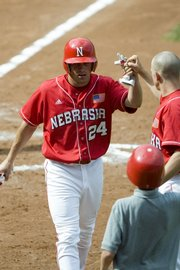 Nebraska's Bryce Nimmo accepts congratulations after scoring against Kansas State. The Cornhuskers won, 5-2, in the Big 12 baseball tournament Friday in Oklahoma City.