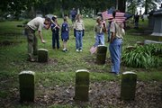 Boy Scouts gather around a row of American Civil War grave stones and mark them with American flags Saturday, May 24, 2008 at Oak Hill Cemetery. The troops were marking the civil war veterans' grave stones for the Sons of Union Veterans of the Civil War.