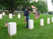 Mark VanEyck, 6, a Bear Scout with Olathe Cub Scout Pack 3777, erects an American flag in front of a headstone at the Leavenworth National Cemetery Saturday. Boy Scouts and Cub Scouts from Leavenworth and surrounding counties laid roughly 30,000 flags in preparation for Monday's Memorial Day ceremony.
