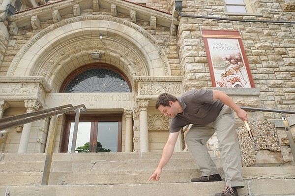Tristan Smith, visitor services coordinator for the Natural History Museum at Dyche Hall, points out fossils in the steps to the building. They are more visible after rainfall. Dyche Hall has been nominated as one of the state's eight architectural wonders.