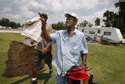Renaissance Village trailer park resident Derrick Williams, right, and his friend Larry Jackson haul items to the Dumpster Saturday in Baker, La., as Williams prepares to move from the FEMA site to a nearby apartment. FEMA is trying to close its last six trailer parks in Louisiana by today.