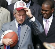 President Bush stands with Kansas basketball guard Russell Robinson, right, as he puts on a hat during a ceremony in the Rose Garden of the White House in Washington, Tuesday, June 3, 2008, to honor the 2008 NCAA men's national basketball championship team from the University of Kansas.
