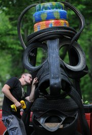 Kansas University senior Jordan Briceland, Wichita, constructs a Moai-influenced head from old tires Tuesday, in preparation for Wakarusa Music and Camping Festival, near the main stage at Clinton Lake State Park. Although the four-day concert begins Thursday, campers are expected to begin showing up today.