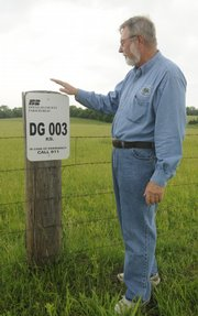 Gary Price, Lawrence, shows a Pasture ID sign Tuesday to let anyone know whom to contact if his livestock get loose or if there is suspicious activity. The program was announced Tuesday for Douglas County.
