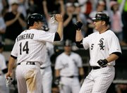 Chicago's Paul Konerko, left, greets Jim Thome after Thome hit a two-run homer. Konerko hit a two-run shot of his own in the 15th inning to sink Kansas City on Wednesday in Chicago.