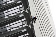 "Alain Robert, known as the French Spider-Man, climbs up The New York Times building Thursday in New York. Robert, who was arrested when he made it to the top, unfurled a banner as he climbed that said ""Global warming kills more people than a 9/11 every week."" Hours later, a second man, identified as Renaldo Clarke of Brooklyn, ascended the 52-story building. He was also taken into custody when he reached the top."
