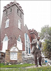 The Rev. Verdell Taylor sweeps the sidewalk in front of St. Luke African Methodist Episcopal Church, 900 N.Y.