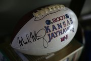 A 2007 Kansas Jayhawk season football, signed by Mark Mangino, sits, ready to be auctioned off.