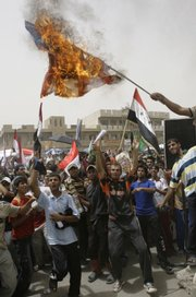 Protesters shout slogans as a burning American flag is waved Friday during a rally in the Shiite enclave of Sadr City, Iraq.