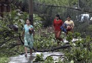 Residents of Yangon, Myanmar, make their way through fallen trees, following cyclone Nargis, in this May 4 file photo. Before the cyclone struck, Yagon was known for its scenic, tree-lined streets.