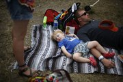 Will Casebeer, of Manhattan, curls up with his godfather, Jim Robertson, of Kansas City, Mo., outside the Yard Dogs Road Show tent. Heavy winds, hail and torrential showers caused some performances to be canceled Sunday evening.