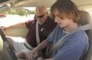 Nick Haley, 15, buckles his seat belt under the supervision of instructor Jon Brown. Nick is taking driver's education classes this summer at Free State High School.