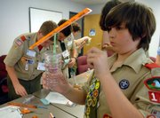 Boy Scout Matthew Murrow makes a wind vane during a Weather Merit Badge Day workshop at the National Oceanic and Atmospheric Administration on Friday at the National Weather Service headquarters in Silver Springs, Md.