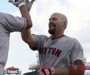 Boston's Kevin Youkilis, right, a childhood Reds fan, is congratulated after his 10th-inning home run against Cincinnati. The Red Sox won, 6-4, Saturday in Cincinnati.