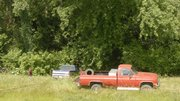 Hillcrest Wrecker workers get ready to pull a truck out of the brush along the levee in North Lawrence during the morning of Tuesday June 17. The truck, owned by John Hey, of rural Baldwin was reported stolen a week ago from the Hey residence.