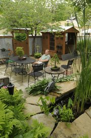 Mike Pisani relaxes in his backyard, where the structures and landscaping have been his longtime pet project. Pisani has been inventive with his use of corrugated steel fencing, sculptures, water garden and use of recycled materials.