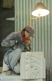 Laura Ramberg works on a 900-pound block of cottonwood limestone in her rural Lawrence shop. The sculpted stone is one of three pieces that Ramberg is completing for the Douglas County Courthouse. Ramberg and Oskaloosa stone carver Keith Middlemas are both sculpting new pieces to replace deteriorated stone sections.