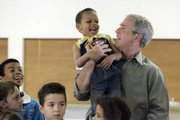 President Bush lifts Dominic Bernier, 3, during a visit to the Red Cross shelter for flood victims Thursday at the Johnson County Fairgrounds in Iowa City, Iowa.