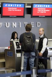 United Airlines first class passengers check in at San Francisco International Airport in this June 4 file photo. Comparing rates of as many airlines as possible is one way to save money on flights this summer.
